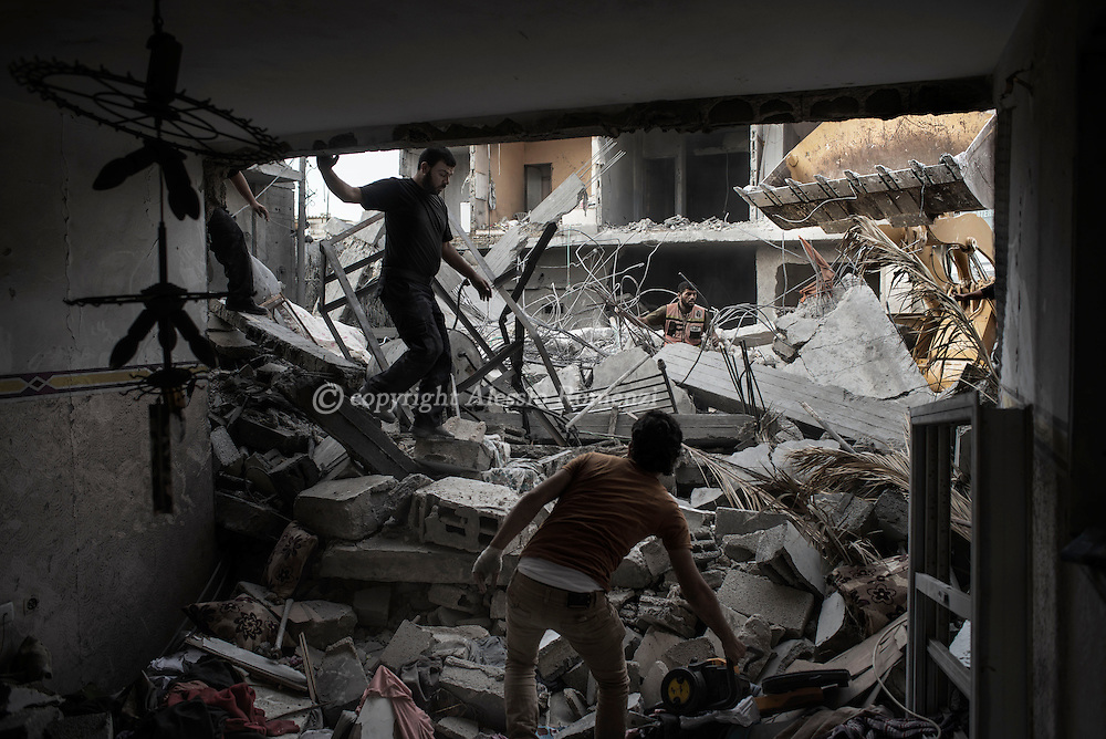 Gaza Strip, Khan Younis: Palestinians search the rubble of destroyed homes where eight members of the Al Haj family were killed in their home by an Israeli air strike early morning in Khan Younis refugee camp, southern Gaza Strip on July 10, 2014. ALESSIO ROMENZI