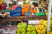 "26 SEPTEMBER 2012 - BANGKOK, THAILAND: A wholesale banana vendor checks his smart phone while he relaxes in Khlong Toey Market in Bangkok. Klong Toey (also called Khlong Toei) Market is one of the largest ""wet markets"" in Thailand. The market is located in the midst of one of Bangkok's largest slum areas and close to the city's original deep water port. Thousands of people live in the neighboring slum area. Thousands more shop in the sprawling market for fresh fruits and vegetables as well meat, fish and poultry.     PHOTO BY JACK KURTZ"