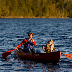 A woman and her son paddle a canoe on Prong Pond in Maine USA