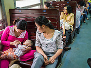 06 APRIL 2012 - HAI PHONG, VIETNAM: A woman and her baby on the Hanoi to Hai Phong Express. The Hanoi to Hai Phong Express Train runs several times a day between Long Bien Station in Hanoi and the Hai Phong Station. Hanoi is the capital of Vietnam and Hai Phong is the 4th largest city in Vietnam. Hai Phong is the principal industrial port in the northern part of Vietnam. It was heavily bombed and mined during the American War (what Americans call the Vietnam War).   PHOTO BY JACK KURTZ