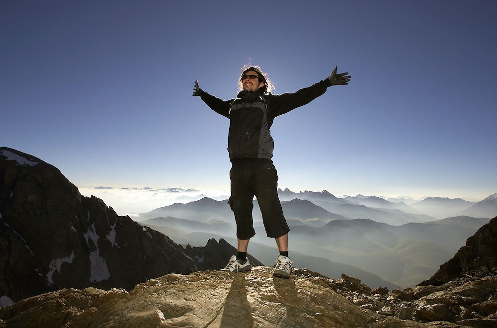 Lifestyle. A man stands on top of a mountain, arms outhstretched embracing the majestic view.