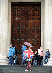 © Licensed to London News Pictures. 26/10/2011. London, UK. Tourists gather in the shelter of the closed doors. Occupy London protesters outside St Paul's Cathedral today, 26 October 2011. The UK's most popular Cathedral still has its doors closed over health and safety fears for it's visitors. Photo: Stephen Simpson/LNP