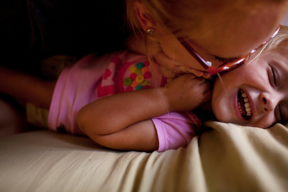 Madelyn Avery Eich, 2, giggles uncontrollably while being kissed and tickled by her mother Melissa, 23, on the afternoon of Saturday, September 11, 2010 in their home in Norfolk, Virginia.