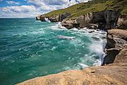 Waves crashing along the rugged coastline south of Tunnel Beach, near Dunedin, New Zealand.