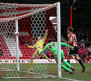 Aiden O'Brien scoring Millwall's second goal during the Sky Bet Championship match between Brentford and Millwall at Griffin Park, London, England on 21 March 2015. Photo by Matthew Redman.