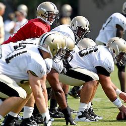 July 29, 2012; Metairie, LA, USA; New Orleans Saints quarterback Drew Brees (9) under guard Brian De La Puente (60) during a training camp practice at the team's practice facility. Mandatory Credit: Derick E. Hingle-US PRESSWIRE