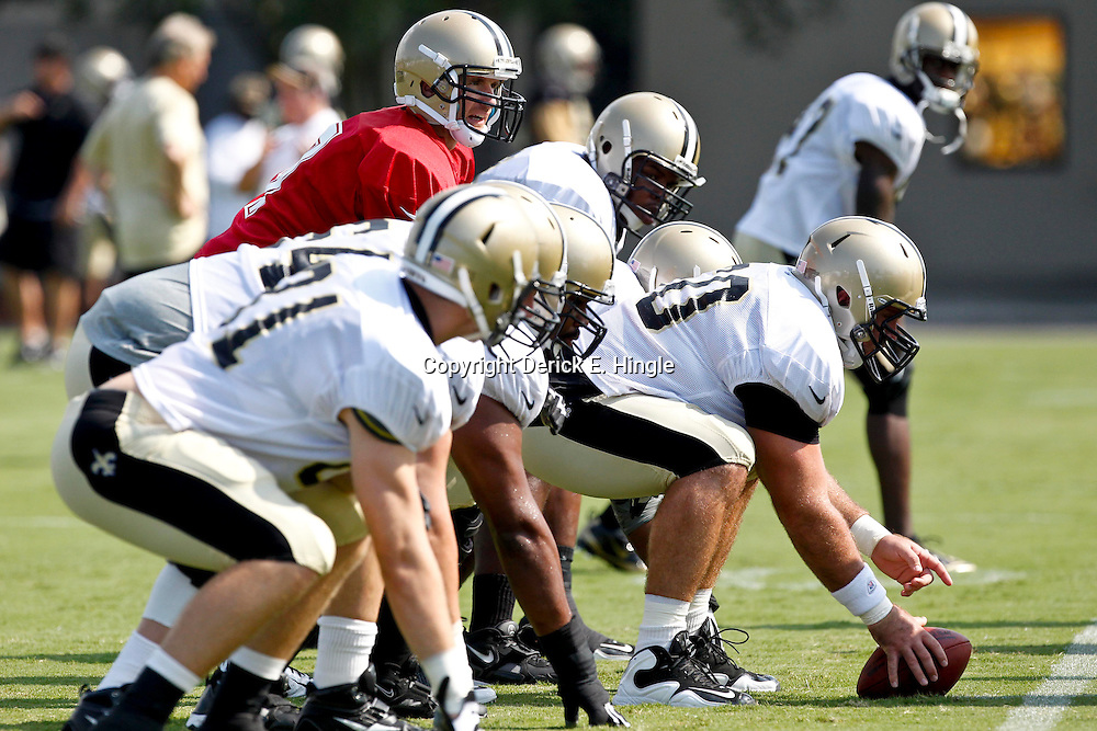 July 29, 2012; Metairie, LA, USA; New Orleans Saints quarterback Drew Brees (9) under guard Brian De La Puente (60) during a training camp practice at the team's practice facility. Mandatory Credit: Derick E. Hingle-US PRESSWIRE