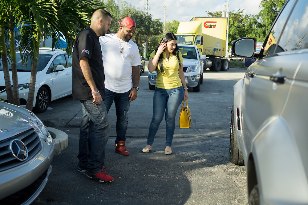 DORAL, FLORIDA, DECEMBER 11, 2015<br /> Alex Vega, left, owner of The Auto Firm, a South Florida car customizing and restoring shop which has a vast clientele of professional athletes and entertainers, delivers a car to client Pablo Sandoval and wife Yulimar Martins in his office. Sandoval was picking up his customized Range Rover.(Photo by Angel Valentin/Freelance)