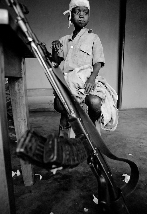 A small tutsi boy in a rebel camp while the fighting for Kigali was raging only a few miles away. he was one of a few survivors from a village where everybody was put in the local church and then attacked with hand grenades.  Apr. 1994 -<br /> The sun had set over the rwandan capital Kigali as president Juvenal Habyarimana's plane approached the city's airport on 6.april 1994.Suddenly, out of the darkness, a rocket hit the plane and sent it crashing to the ground, killing everyone on board.over the next three month's, more than 800.000 rwandans would be murdered, many cut down with machetes, killed by neighbours and countrymen, in a ferocious ethnic genocide that was all but ignored by the international world.