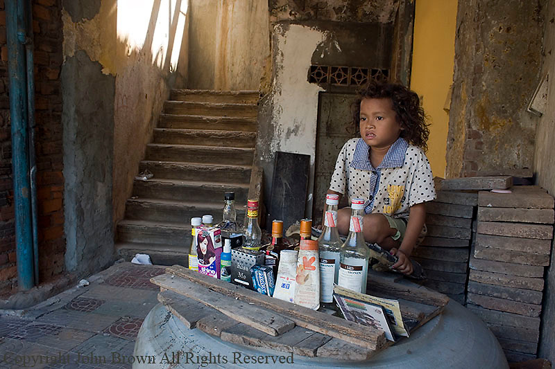 A young girl living in poverty tends to a make believe store she assembled with scavenged garbage at her home in a slum in Kampong Cham, Cambodia.