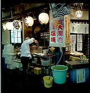 Chef prepares grilled seafood outside a Kabuki-Cho restaurant, Shinjuku, Tokyo, Japan.