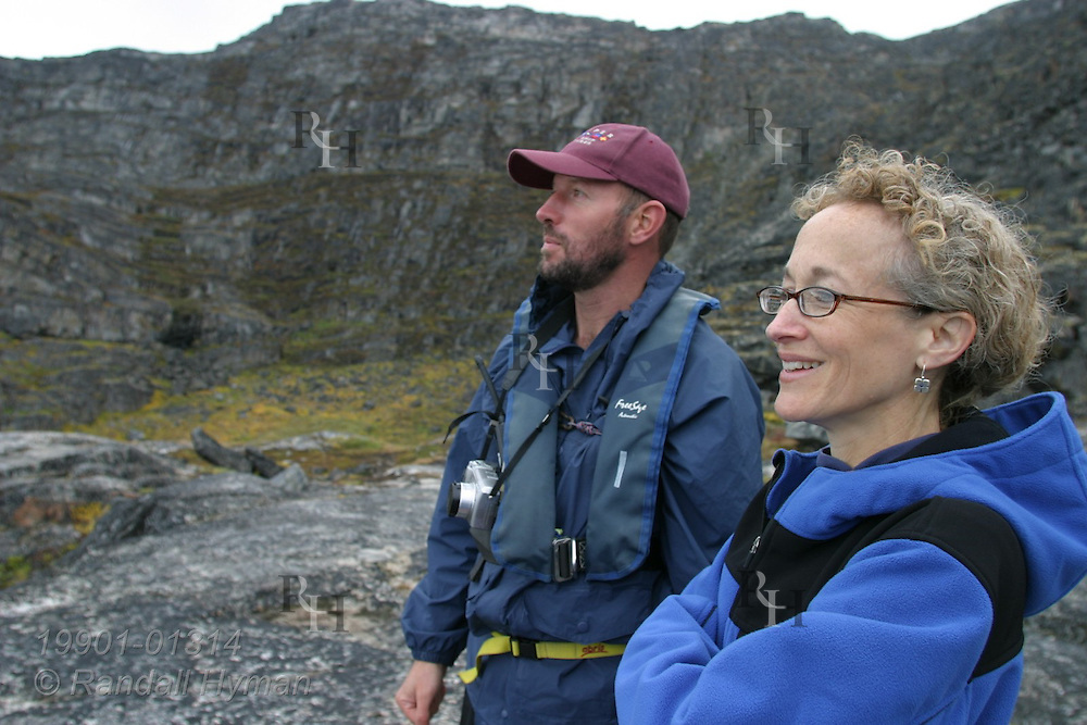 Man and woman from expedition cruise ship Clipper Adventurer stand above Qilakitsoq archaeological site where eight well-preserved 15th-century Inuit mummies were rediscovered in 1972; Uummannaq, Greenland