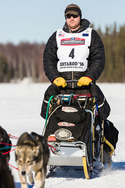 Musher Nathan Schroeder competing in the 44th Iditarod Trail Sled Dog Race on Long Lake after leaving the restart on Willow Lake in Southcentral Alaska.  Afternoon. Winter.