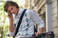 Man sitting on bicycle talking on mobile phone