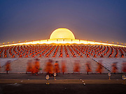 "22 FEBRUARY 2016 - KHLONG LUANG, PATHUM THANI, THAILAND: Monks and novices file into the chedi before the evening service for Makha Bucha Day at Wat Phra Dhammakaya.  Makha Bucha Day is a public holiday in Cambodia, Laos, Myanmar and Thailand. Many people go to the temple to perform merit-making activities on Makha Bucha Day, which marks four important events in Buddhism: 1,250 disciples came to see the Buddha without being summoned, all of them were Arhantas, Enlightened Ones, and all were ordained by the Buddha himself. The Buddha gave those Arhantas the principles of Buddhism, called ""The ovadhapatimokha"". Those principles are:  1) To cease from all evil, 2) To do what is good, 3) To cleanse one's mind. The Buddha delivered an important sermon on that day which laid down the principles of the Buddhist teachings. In Thailand, this teaching has been dubbed the ""Heart of Buddhism."" Wat Phra Dhammakaya is the center of the Dhammakaya Movement, a Buddhist sect founded in the 1970s and led by Phra Dhammachayo. The temple is famous for the design of its chedi, which some have likened to a flying saucer or UFO.            PHOTO BY JACK KURTZ"
