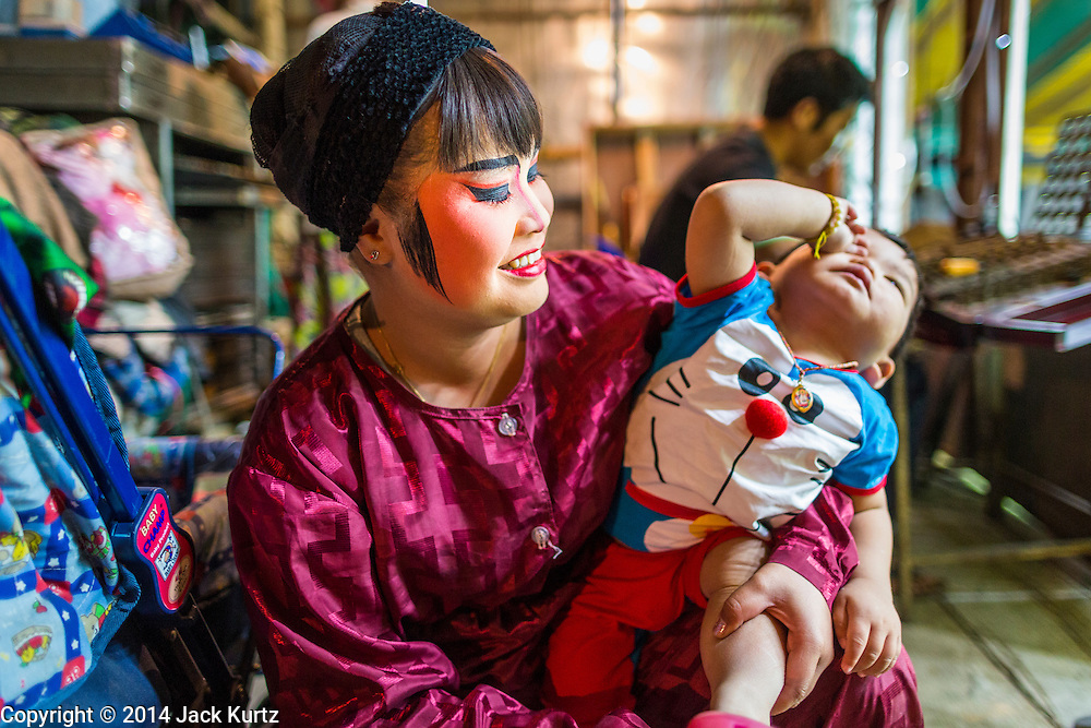 "25 JANUARY 2014 - BANG LUANG, NAKHON PATHOM, THAILAND: A member of the Sing Tong Teochew opera troupe comforts her baby before a show. The Sing Tong Teochew opera troupe has been together for 60 years and travels through central Thailand and Bangkok performing for mostly ethnic Chinese audiences.  Chinese opera was once very popular in Thailand, where it is called ""Ngiew."" It is usually performed in the Teochew language. Millions of Chinese emigrated to Thailand (then Siam) in the 18th and 19th centuries and brought their cultural practices with them. Recently the popularity of ngiew has faded as people turn to performances of opera on DVD or movies. There are still as many 30 Chinese opera troupes left in Bangkok and its environs. They are especially busy during Chinese New Year when travel from Chinese temple to Chinese temple performing on stages they put up in streets near the temple, sometimes sleeping on hammocks they sling under their stage.     PHOTO BY JACK KURTZ"