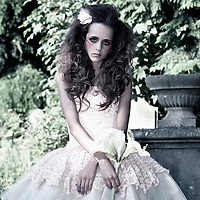 Female youth with sad expression holding flower wearing white dress standing in graveyard
