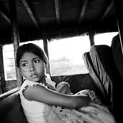 A young girl peers around nervously as the bus she is travelling on slows at a checkpoint near Puerto Asis, Putumayo.