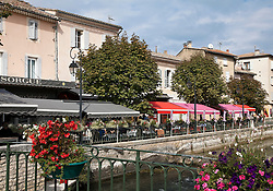 The brightly colored awnings of outdoor cafes line the edges of the  Sorgue River as it encircles the heart of L'Isle-sur-la-Sorgue in the Luberon district of Provence in southern France.  Known for its twice a week antiques markets and numerous antique and design shops open daily, this market town is high on many visitors' lists.