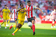 Alim Ozturk (#5) of Sunderland AFC is tackled by Michael Folivi (#17) of AFC Wimbledon during the EFL Sky Bet League 1 match between Sunderland and AFC Wimbledon at the Stadium Of Light, Sunderland, England on 24 August 2019.