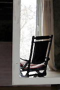 comfort rocking chair in front of large window looking out over a snowed under landscape