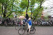 In Utrecht fietst een moeder met twee kinderen, waarvan er eentje achterop de bagagedrager staat, door de binnenstad.<br /> <br /> In downtown Utrecht a mother cycles with two boy, one standing on the carrier of a bike.