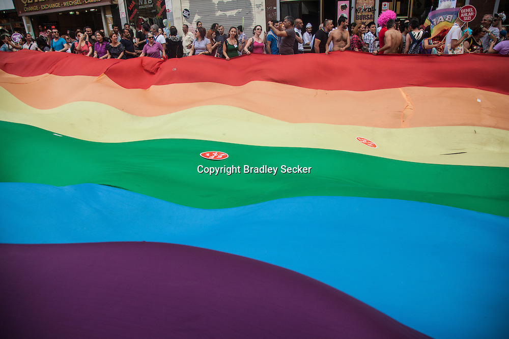 Participants at Istanbul Pride carry a large rainbow flag from Taksim along Istiklal, one of the city's main avenues. Istanbul, Turkey, 2013