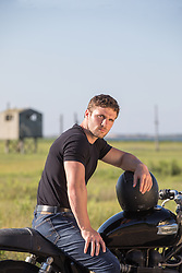 good looking man sitting on a motorcycle on rural road