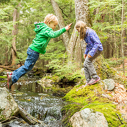 A jumps over a small stream in the Stonehouse Forest in Barrington, New Hampshire.