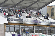 Rain Stops Play - A spectators shelter under the roof of the Somerset Stand as the heavy rain continues to fall during the Specsavers County Champ Div 1 match between Somerset County Cricket Club and Essex County Cricket Club at the Cooper Associates County Ground, Taunton, United Kingdom on 23 September 2019.