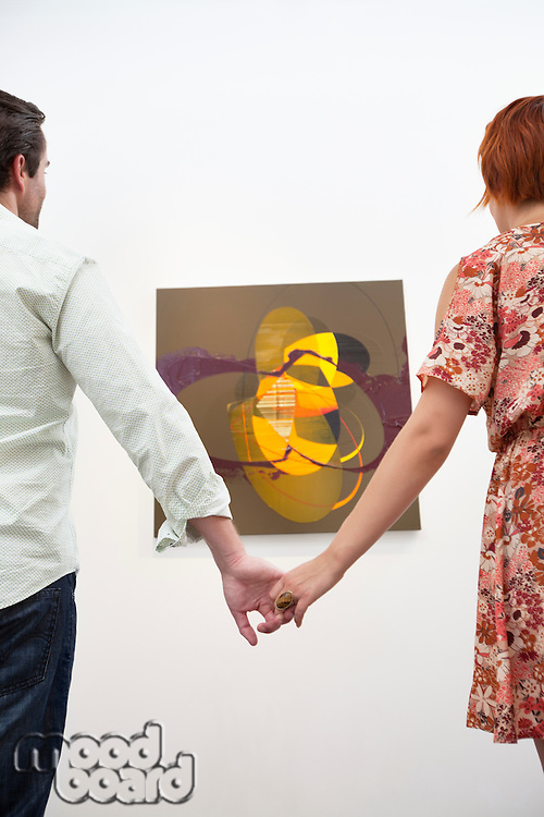 Married couple holding hands in front of painting in museum