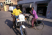 Ghananian immigrants riding motorcycle and bicycle along Torre steet (center of the village) in Nonantola, Saturday, Jun 27, 1996...Immigrati ghanesi in moto e bicicletta in via della Torre a Nonantola.