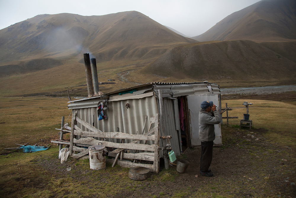 September 16 2016 A shepherd uses old Soviet binoculars to scan the horizon to see if he had left any cattle out in an approaching storm in the upper reaches of the Chon Kemin Valley. Climate change in Kyrgyzstan is affecting cross border water rights in the already ethnically divided Fergana Valley, all while glaciers melt in the Tian Shan Mountains. Tensions are rising as different groups compete for scarcer and scarcer resources.