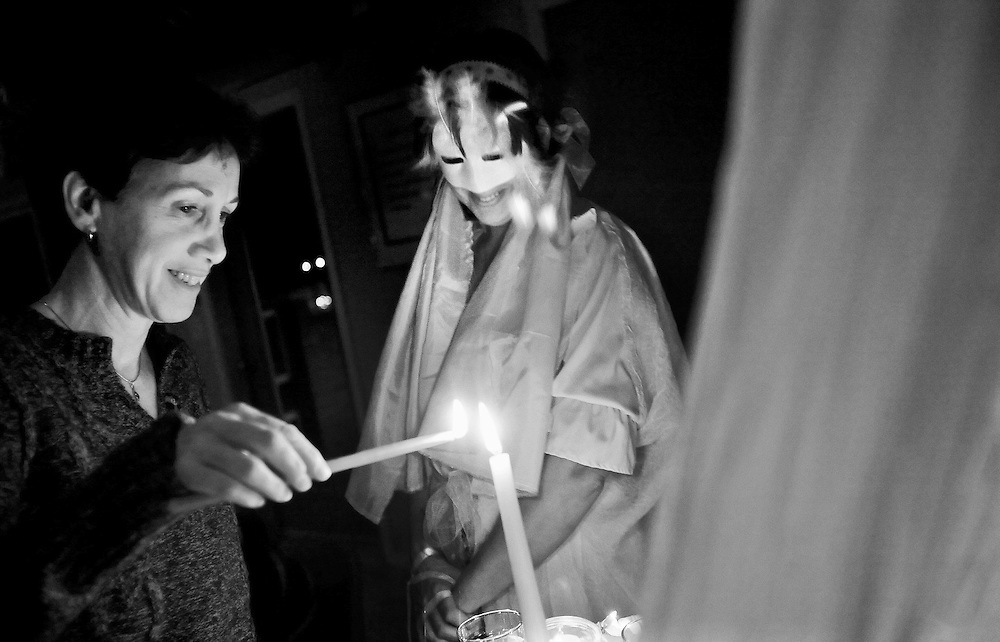 Laureen Blakemore, GUARDIAN OF THE EAST (middle, with mask), watches as Lisa Evanylo lights a candle and makes a wish at the East Alter during a Winter Solstice Ritual at The Unitarian Universalist Congregation in Blacksburg on Thursday night. The Solstice happens twice a year, when the Sun is at its greatest distance from the celestial equator, and the Winter Solstice marks the shortest day and the longest night of the year.