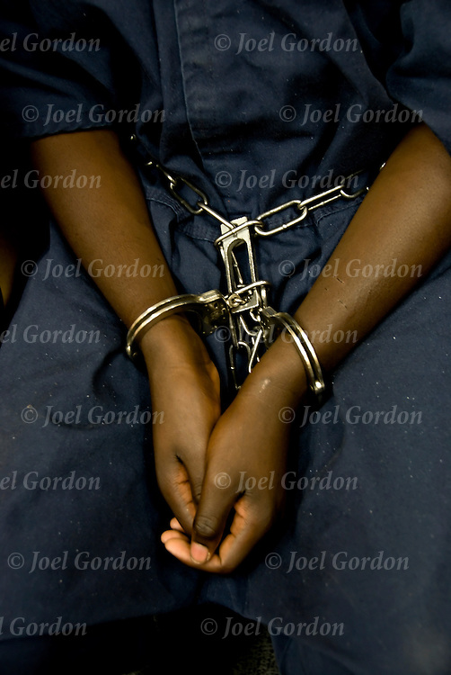 Juveniles in handcuffs and leg irons standing or sitting in the Juvenile Court