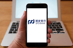 Using iPhone smartphone to display logo of SPD, Shanghai Pudong, Development Bank, Chinese commercial bank.