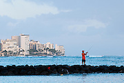 A fisherman casts of a jetty along Waikiki Beach in Hawaii.