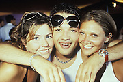 Boy with sunglasses and two girls posing for a picture. Ibiza 1999.