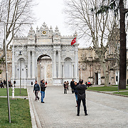 Tourists outside the main gate (the Gate f the Sultans) at Dolmabahçe Palace. Dolmabahçe Palace, on the banks of the Bosphorus Strait, was the administrative center of the Ottoman Empire from 1856 to 1887 and 1909 to 1922. Built and decorated in the Ottoman Baroque style, it stretches along a section of the European coast of the Bosphorus Strait in central Istanbul.