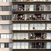 People in a Vancouver apartment building look over the Pride Parade.