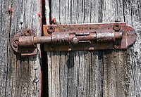 Rusted metal door hasp attached to weathered antique wooden barn door with robertson screws