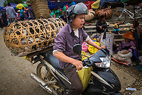 BAC HA, VIETNAM - CIRCA SEPTEMBER 2014:  Vietnamese man riding motorbike at the Bac Ha sunday market, the biggest minority people market in Northern Vietnam