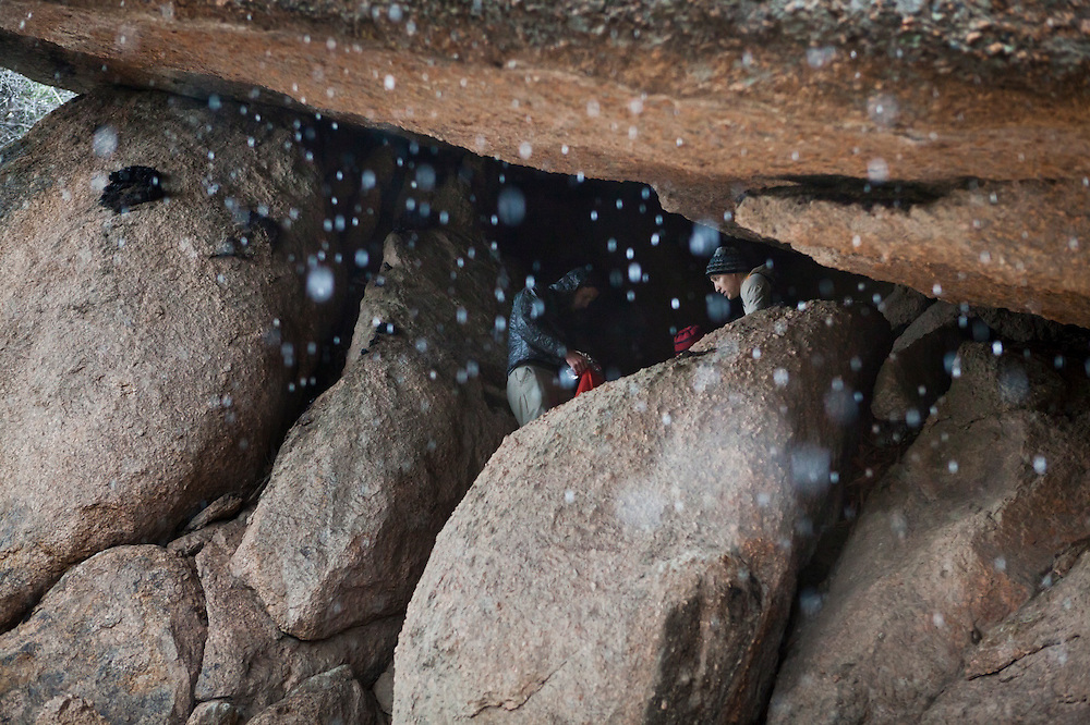 David Coffey (r-l), Marco Binotti, and Obadiah Reid take shelter from a snow storm inside a small cave in the Lost Creek Wilderness, Colorado.