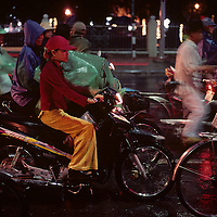 Asia, Vietnam, Hué, Young woman sits on motorcycle at traffic light in rain on Phu Xuan Bridge across Mekong River