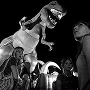 People seem undaunted by the looming T-Rex at the Iowa State Fair midway, in Des Moines, Iowa.