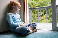 Young girl (5-6) sitting cross-legged at carpet looking through balcony door