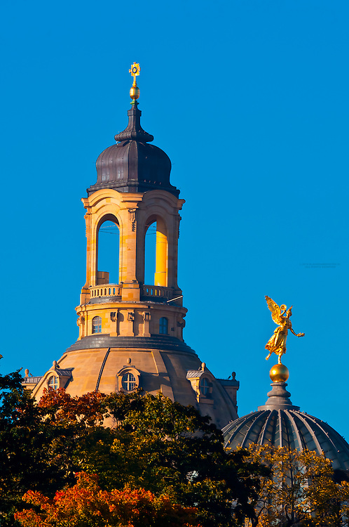 """Statue of an angel holding the """"Trumpet of Fame"""" atop the glass dome known as the Lemon Squeezer (Zitronenpresse) on the Kunstakademie (Art Academy) with the Frauenkirche (church) behind, Dresden, Saxony, Germany"""