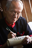 Man completes a traditional drawing on bamboo in a demonstration of Bidayuh handicraft and art a the Sarawak Cultural Village.