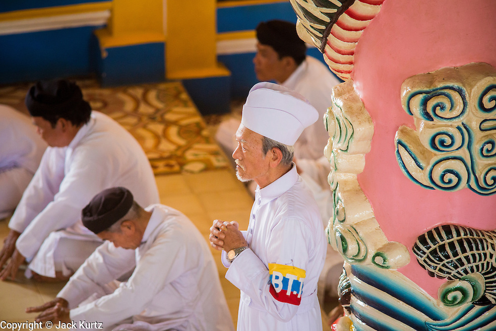 """29 MARCH 2012 - TAY NINH, VIETNAM:  Cao Dai clergy, in colored robes, and adherents, in white, during noon services at the Cao Dai Holy See in Tay Ninh, Vietnam. Cao Dai (also Caodaiism) is a syncretistic, monotheistic religion, officially established in the city of Tây Ninh, southern Vietnam in 1926. Cao means """"high"""" and """"Dai"""" means """"dais"""" (as in a platform or altar raised above the surrounding level to give prominence to the person on it). Estimates of Cao Dai adherents in Vietnam vary, but most sources give two to three million, but there may be up to six million. An additional 30,000 Vietnamese exiles, in the United States, Europe, and Australia are Cao Dai followers. During the Vietnam's wars from 1945-1975, members of Cao Dai were active in political and military struggles, both against French colonial forces and Prime Minister Ngo Dinh Diem of South Vietnam. Their opposition to the communist forces until 1975 was a factor in their repression after the fall of Saigon in 1975, when the incoming communist government proscribed the practice of Cao Dai. In 1997, the Cao Dai was granted legal recognition. Cao Dai's pantheon of saints includes such diverse figures as the Buddha, Confucius, Jesus Christ, Muhammad, Pericles, Julius Caesar, Joan of Arc, Victor Hugo, and the Chinese revolutionary leader Sun Yat-sen. These are honored at Cao Dai temples, along with ancestors.      PHOTO BY JACK KURTZ"""