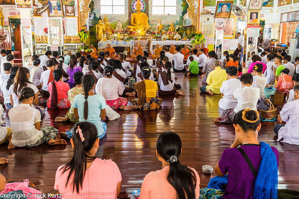 24 MAY 2013 - MAE SOT, THAILAND:   Burmese gather in Wat Pha Mai for Visakha Puja Day services. Visakha Puja (Vesak) marks three important events in the Buddha's life: his birth, his attainment of enlightenment and his death. It is celebrated on the full moon of the sixth lunar month, usually in May on the Gregorian calendar. This year it is on May 24 in Thailand and Myanmar. It is celebrated throughout the Buddhist world and is considered one of the holiest Buddhist holidays. Burmese Buddhist in Mae Sot celebrated with a procession through Mae Sot that ended with a service followed by a communal meal at Wat Pha Mai, the most important Burmese Buddhist temple in Mae Sot.   PHOTO BY JACK KURTZ